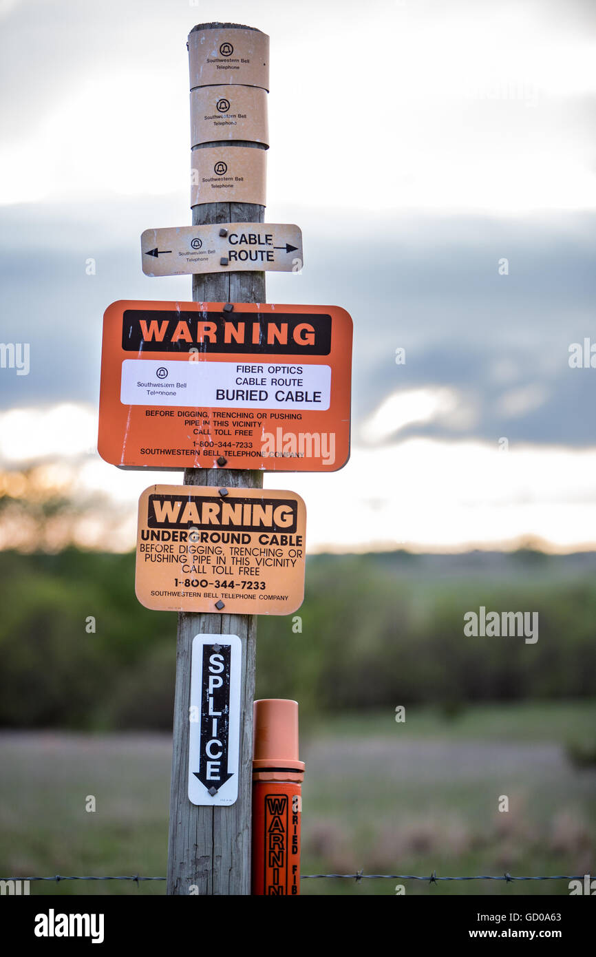 Sign warning that fiber optic cable is buried below. - Stock Image