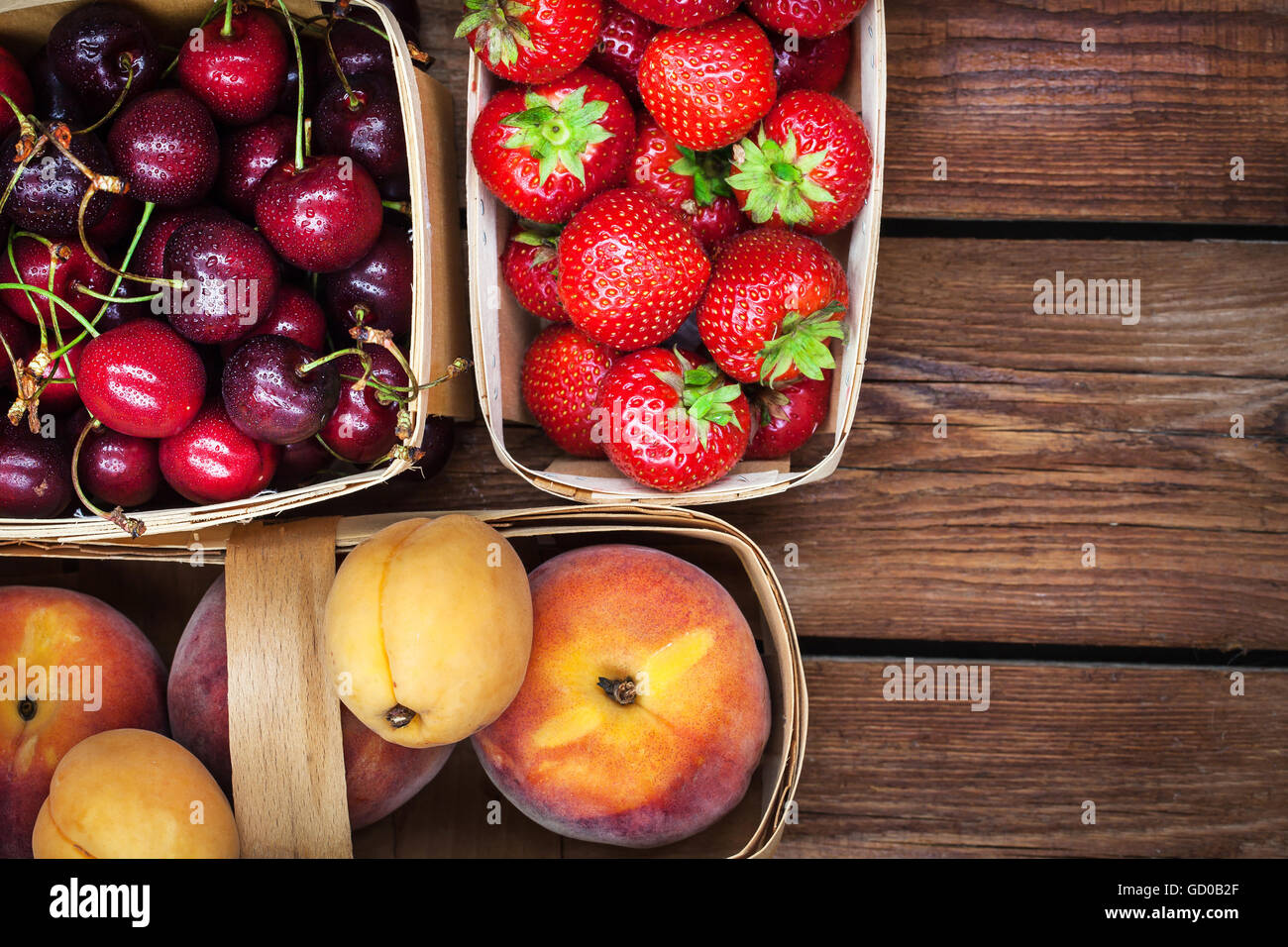 Fresh ripe summer berries and fruits (peaches, apricots, cherry, strawberry) in baskets, top view - Stock Image