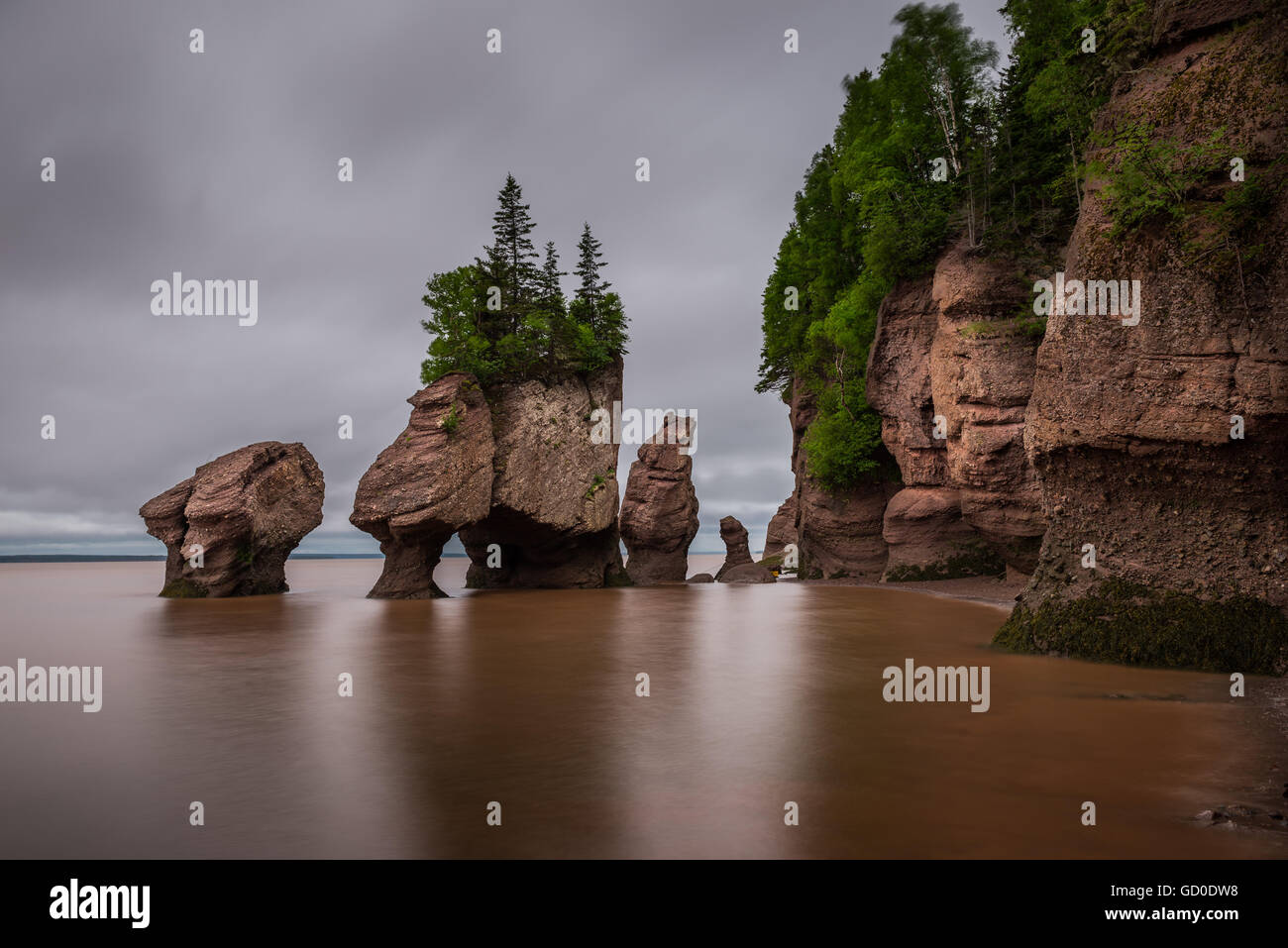 A long exposure of the Flowerpot Rocks, part of the Hopewell Rocks, in New Brunswick, Canada. - Stock Image