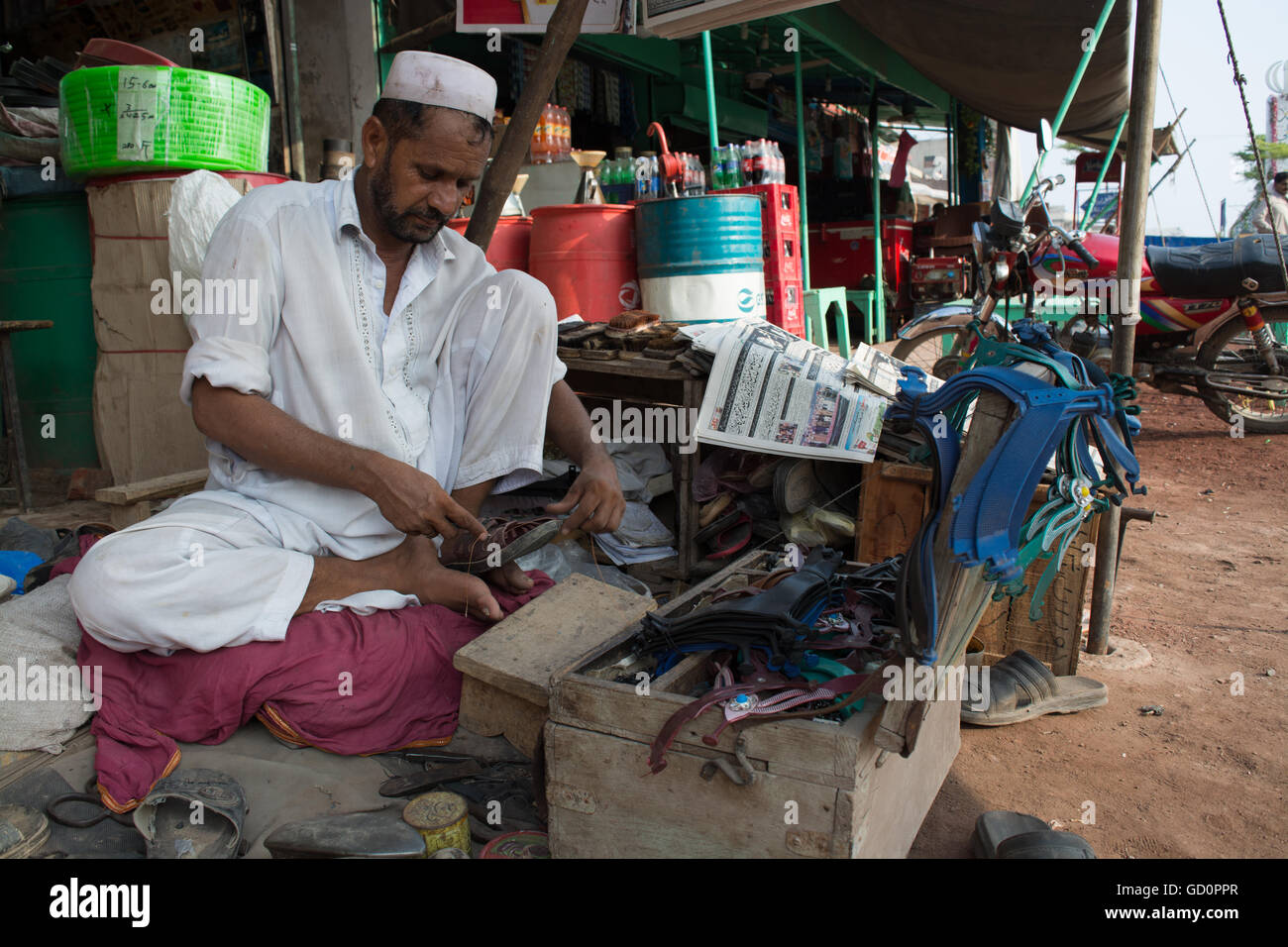 A cobbler is repairing shoes on roadside to earn money for his family even in hot weather on main road of city Pindi - Stock Image