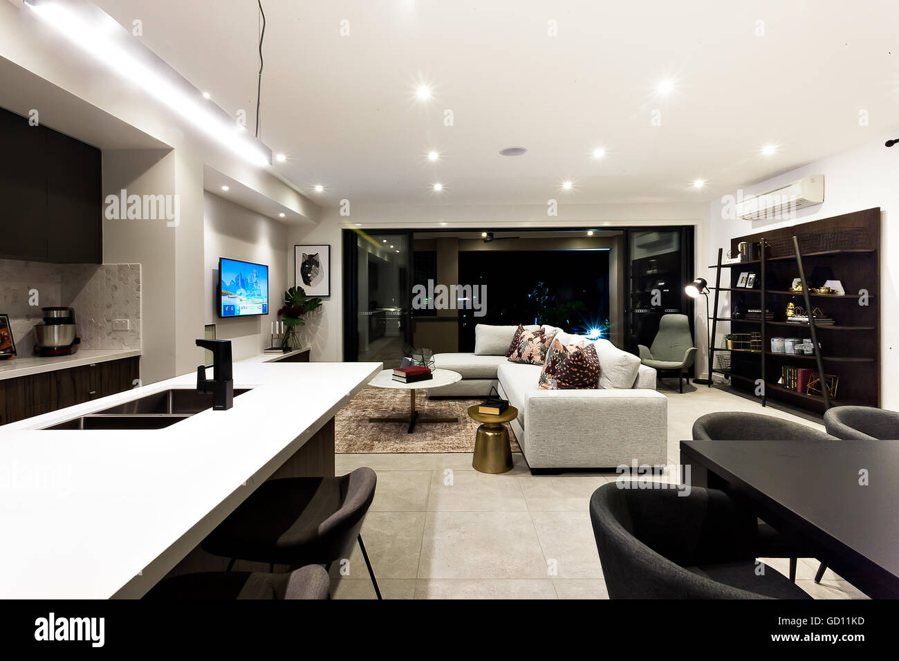 Creative living room including kitchen, dinner, shelf and living room next to outside patio area at night - Stock Image