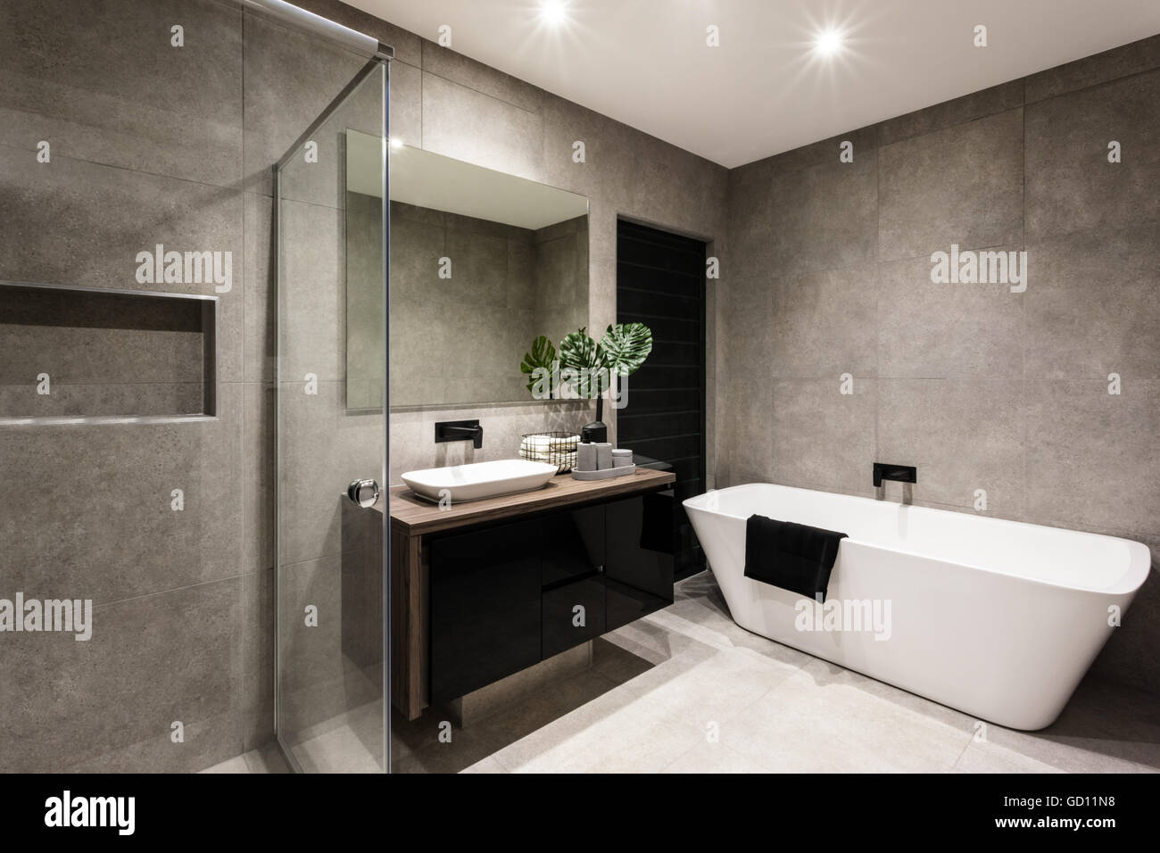 Modern Bathroom With A Shower Area And Bath Tub Including A Wall Mirror  Beside A Fancy Plant Near A Tap And Sink Over The Wooden