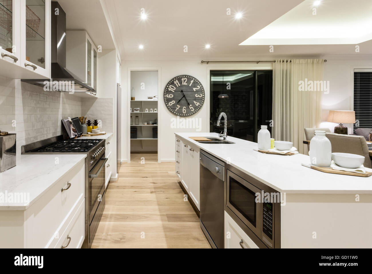 Luxury kitchen through the hallway to a another room between stoves, oven, counter top and cupboards beside a big - Stock Image