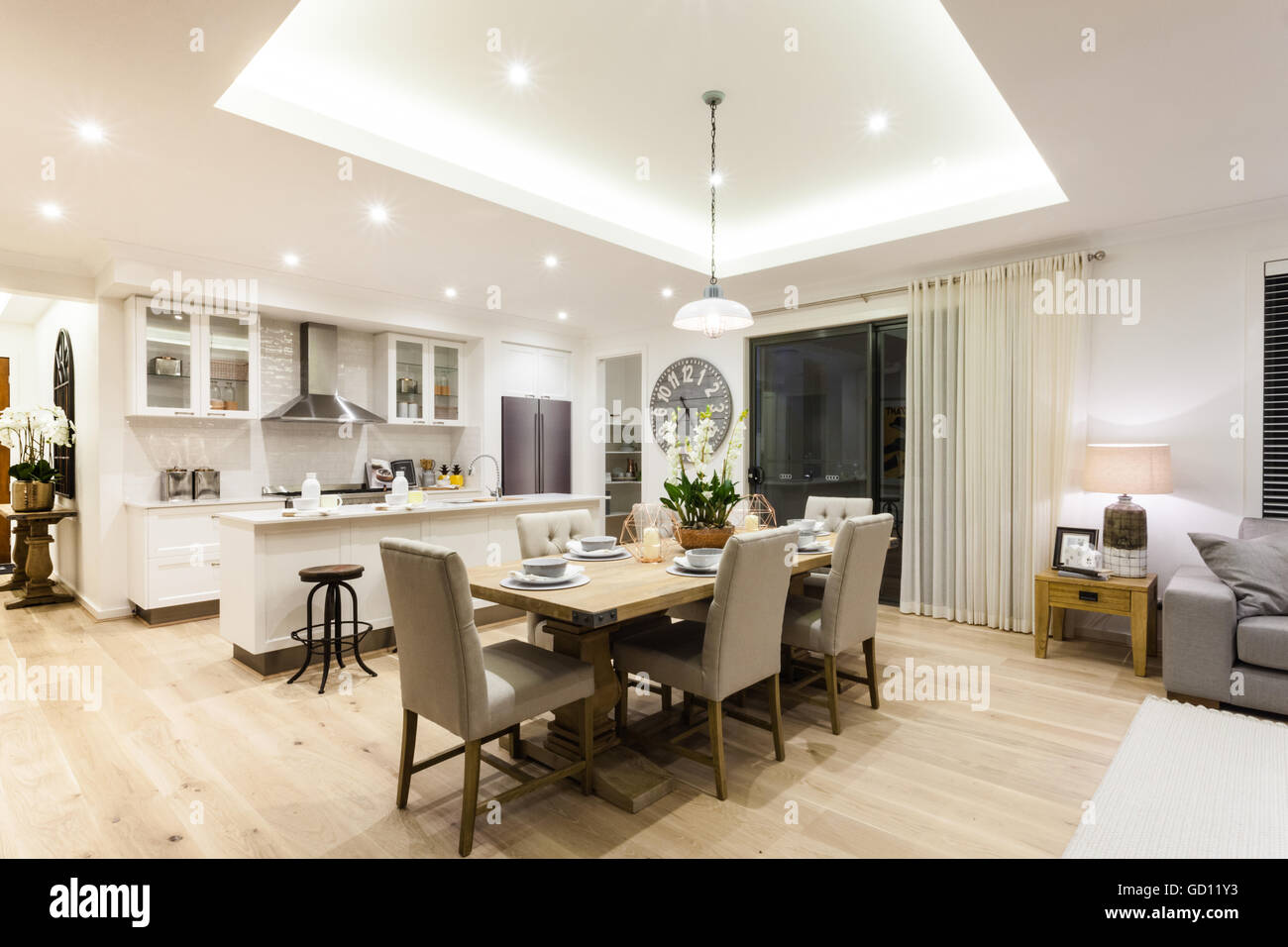 Modern living room and kitchen with a wooden floor illuminated at night with lights - Stock Image