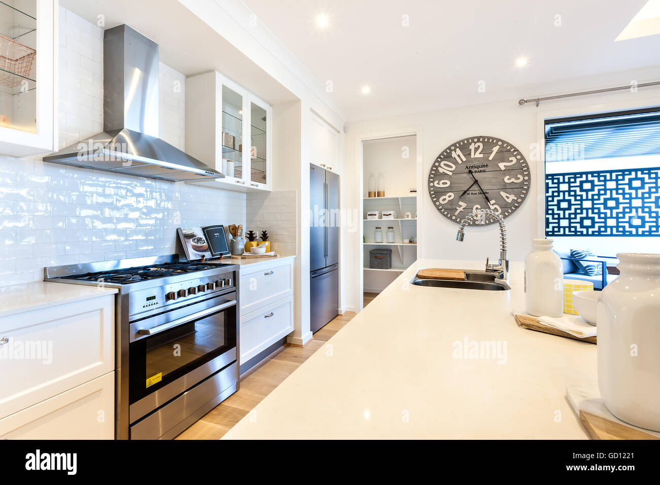 Luxury kitchen closeup with counter top and stove under the oven next to drawer with cabinets beside a big wooden Stock Photo