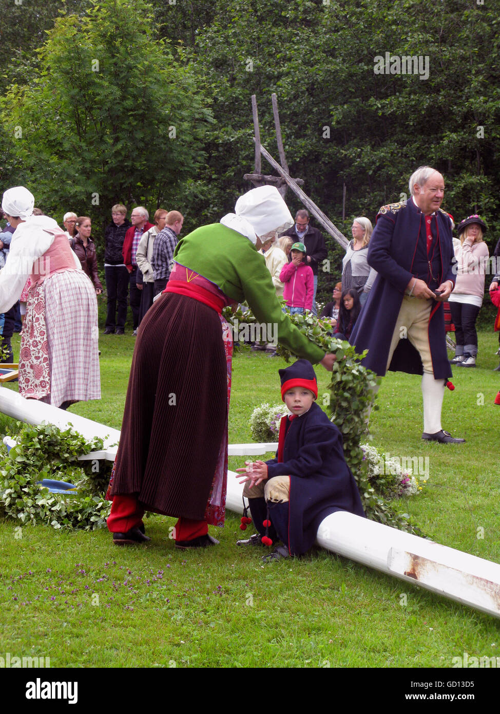 MIDSUMMER people of all age in costumes preparing the festivities - Stock Image