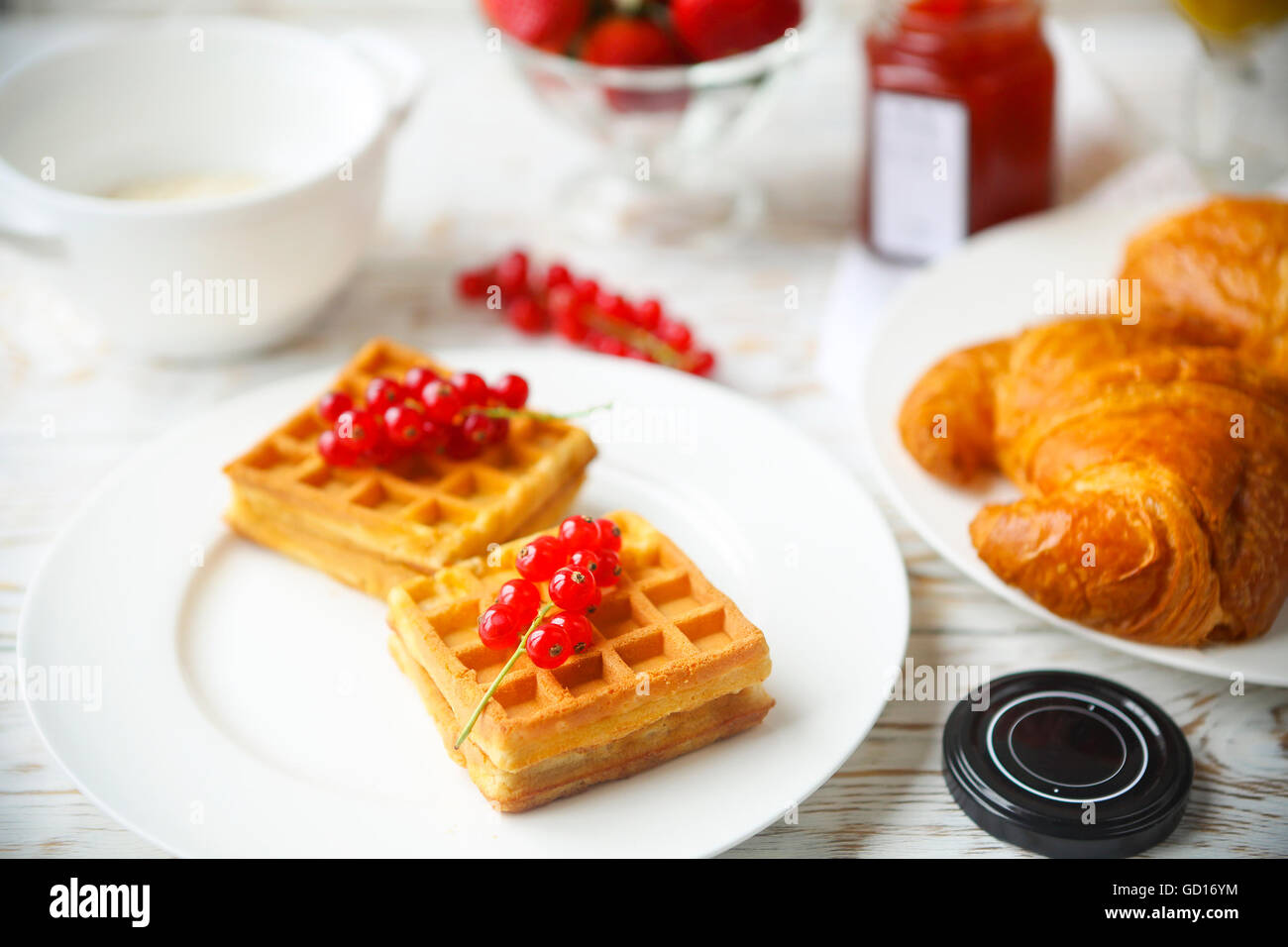 Waffles with red currant jam and berries on a white plate, croissants, orange juice and oat flakes oatmeal on the Stock Photo
