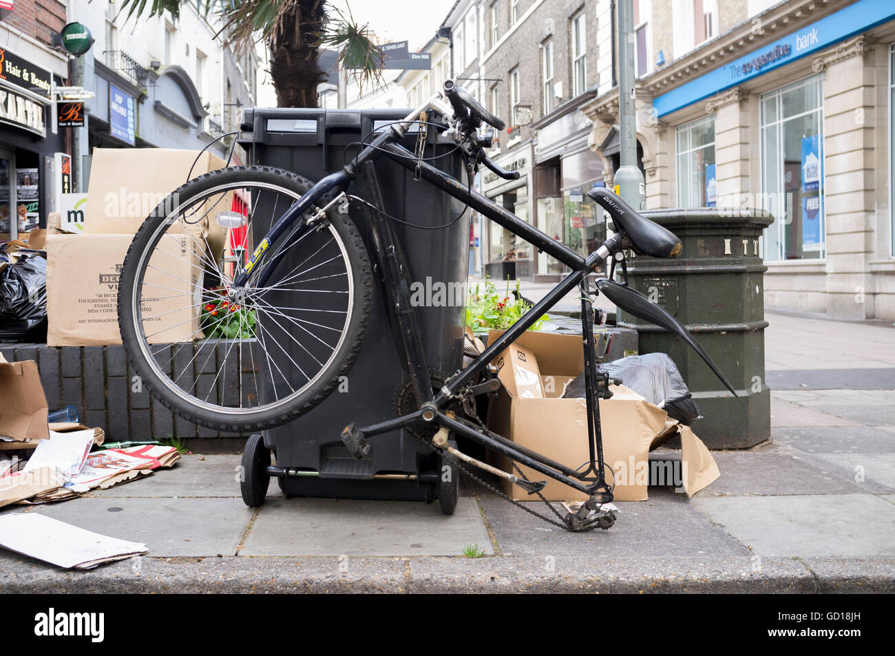Mountain bike dumped by rubbish bin - Stock Image