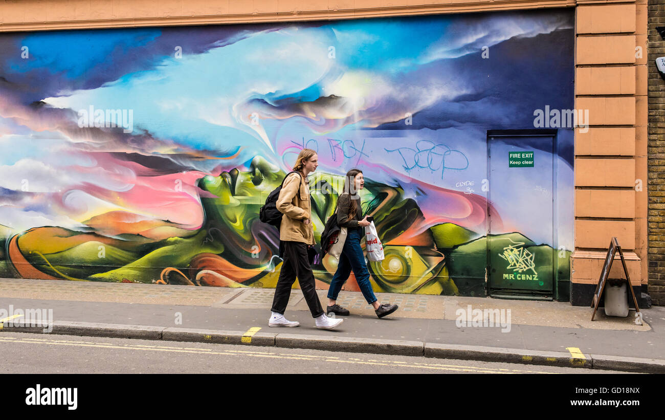 Hipster couple walking in front of a graffiti in a street in Soho, a trendy area in London famous for restaurants - Stock Image