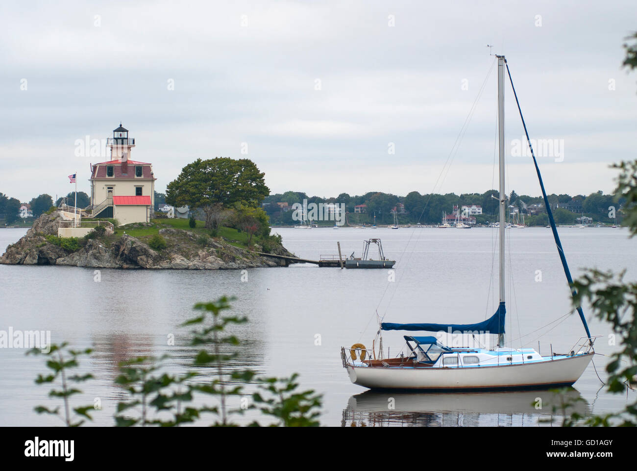 Sailboat anchored by Pomham Rocks lighthouse on a cloudy day in Rhode Island. - Stock Image
