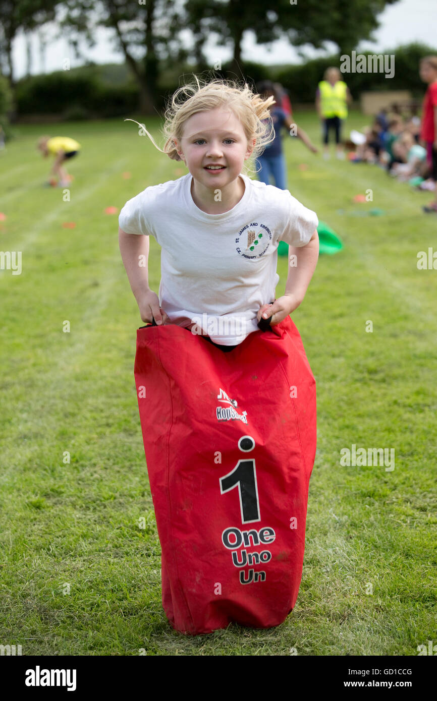 Girl competing in sack race school sports day Chipping Campden UK - Stock Image