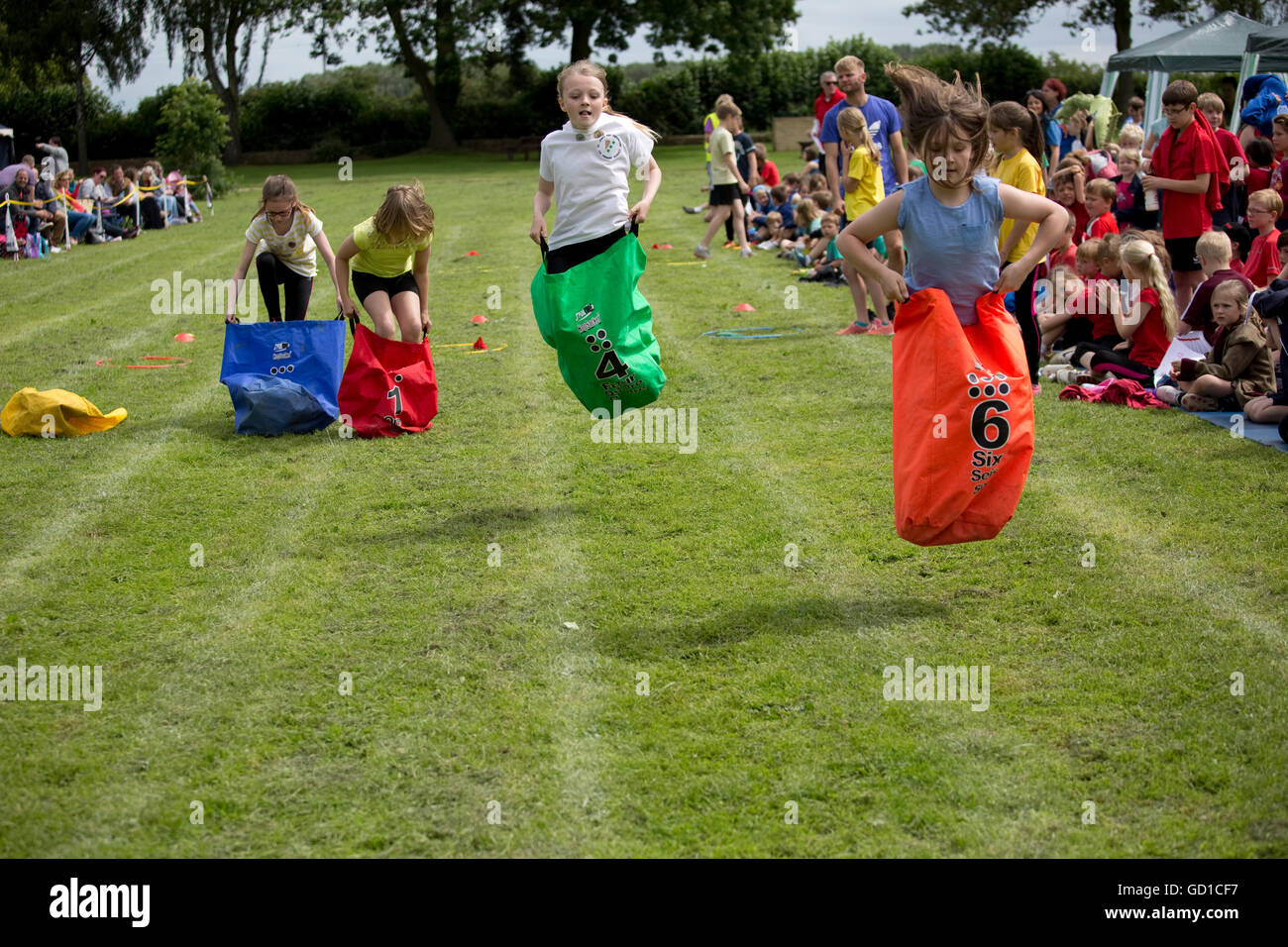 Girls competing in sack race St James Primary School sports day Chipping Campden UK - Stock Image