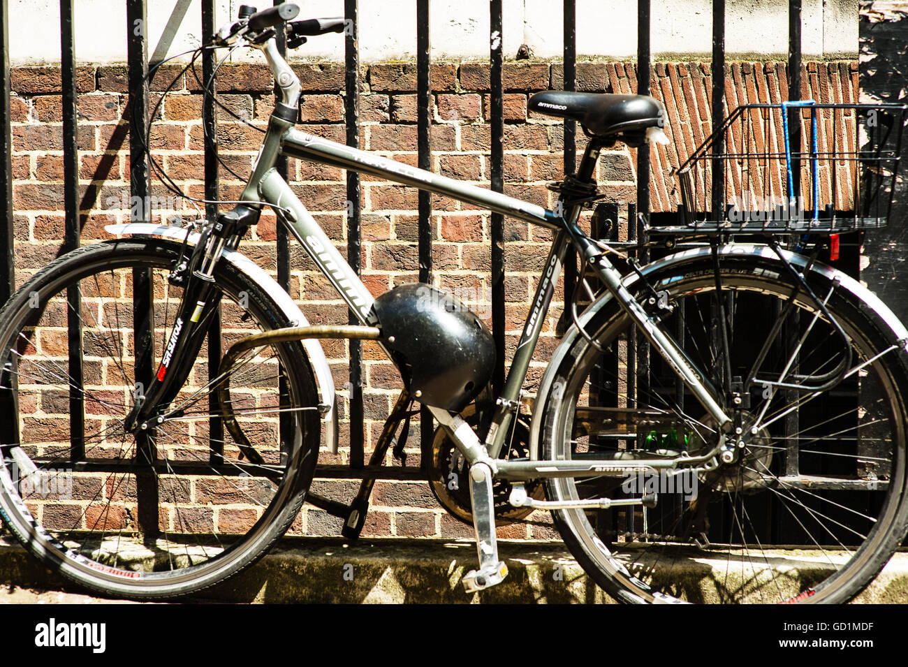 Image of a Bicycle Secured To An Iron Or Steel Railing Fence In London - Stock Image