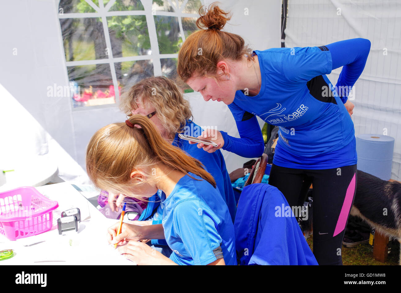 Organizers and judges marking the results in dog agility competitions. Three girls in a tent, writing down the results. - Stock Image