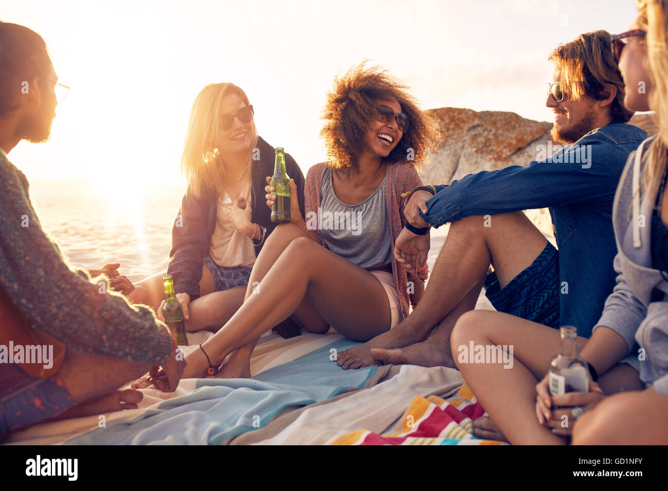 Mixed race friends having fun at the beach. Group of happy young people sitting together at the beach talking and drinking beers Stock Photo