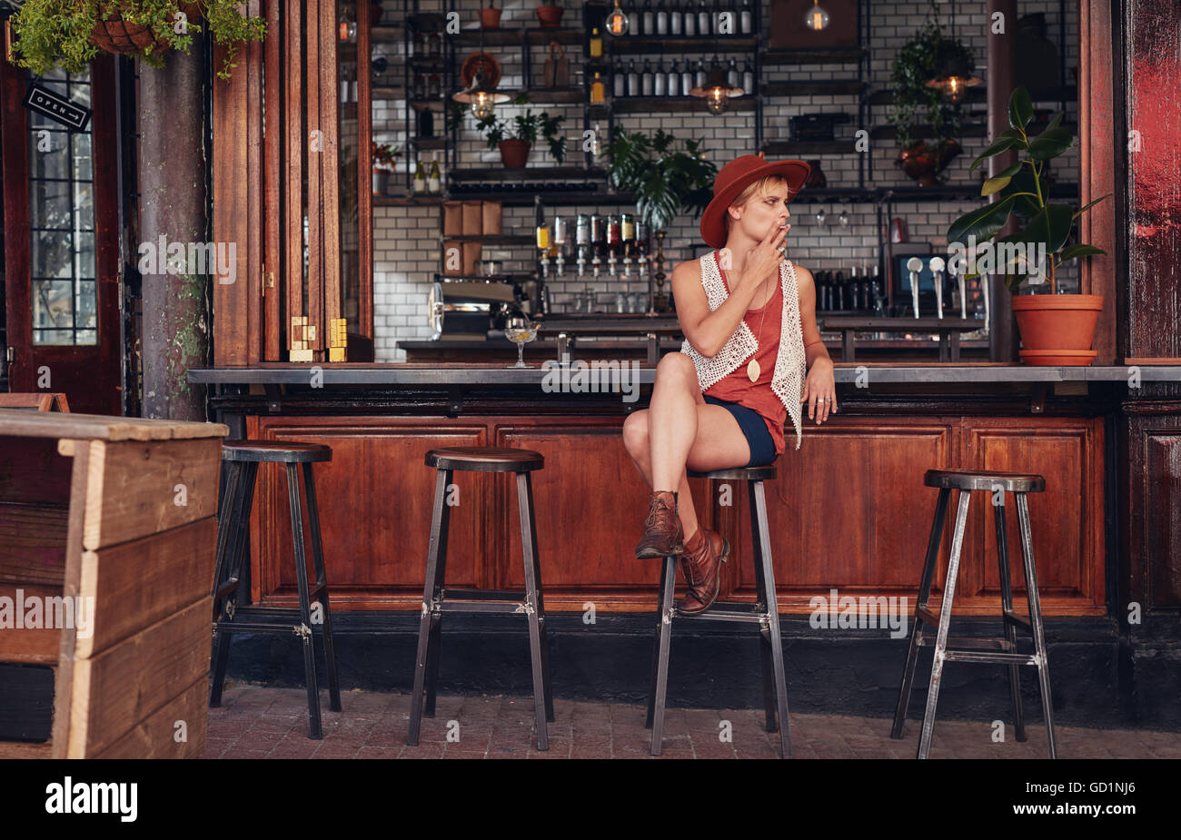 Young woman with hat smoking in a bar. Holding cigarette and looking away. - Stock Image
