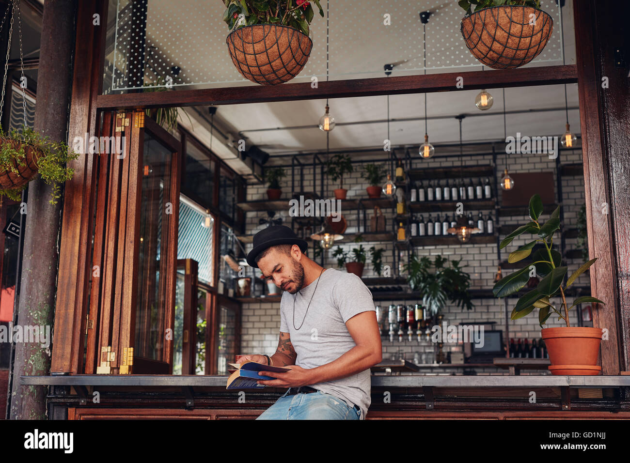 Portrait of relaxed young man sitting at a cafe counter reading a book. Stylish young guy reading novel while sitting - Stock Image