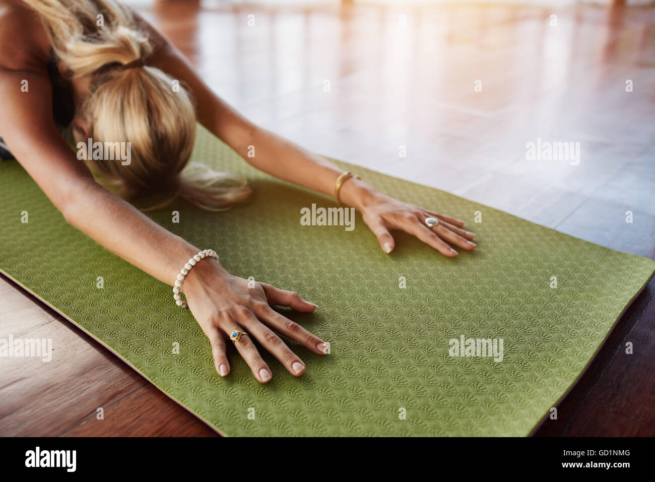 Female doing stretching workout on exercise mat. Woman doing balasana yoga at gym, with focus on hands. - Stock Image