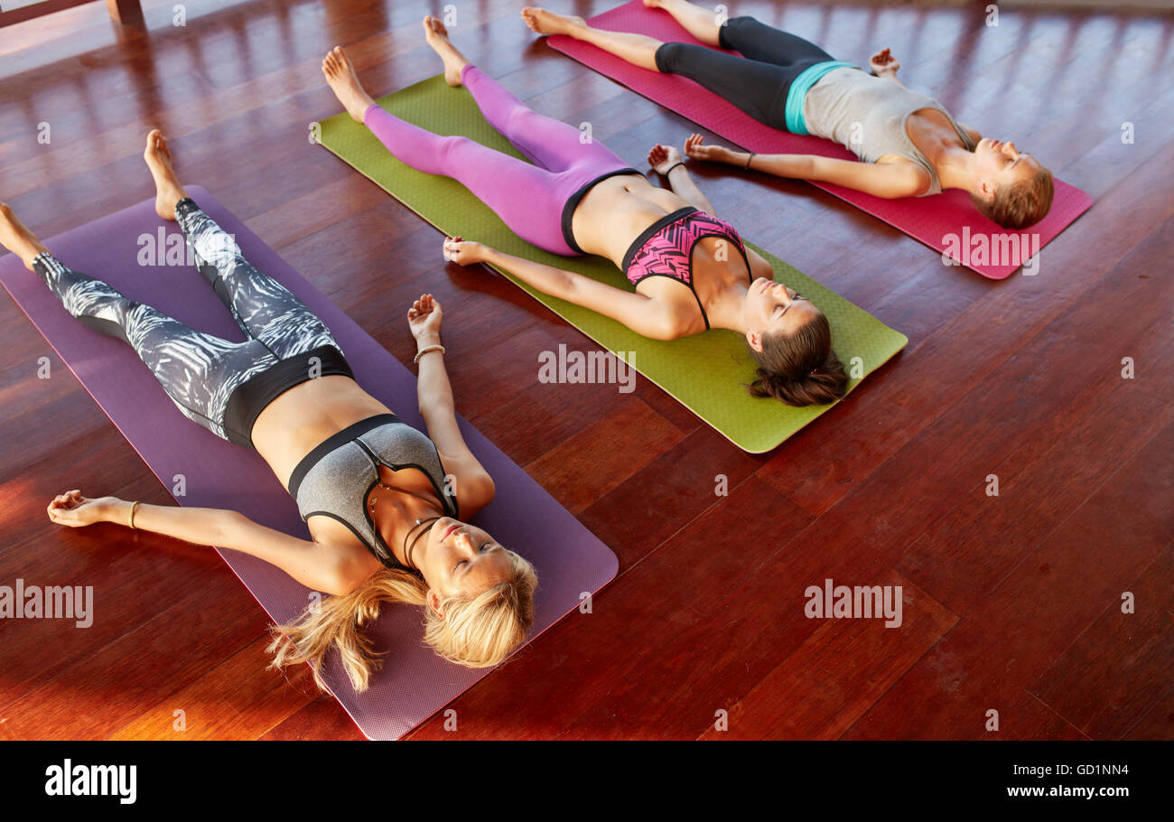 Top view shot of yoga class with young women relaxing on fitness mat. Group of females lying on floor after workout Stock Photo