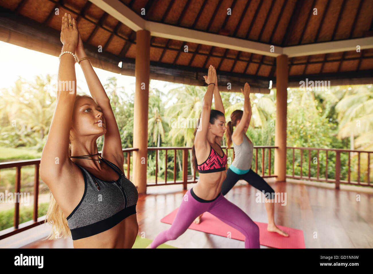 Shot of women standing with their hands joined overhead. Healthy group of young female exercising at yoga class. - Stock Image