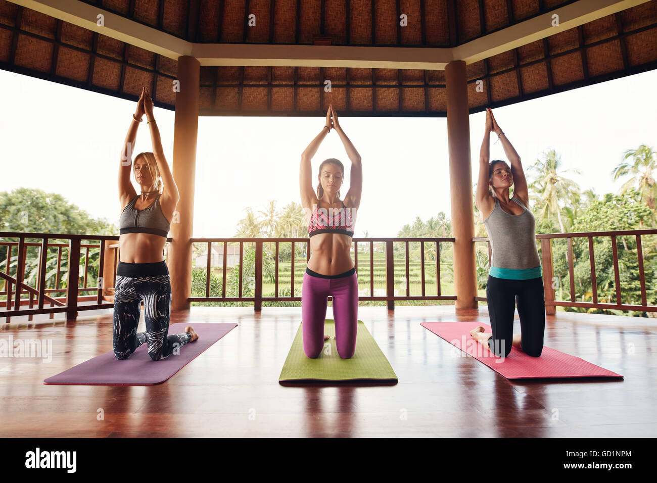 Shot of three young women doing yoga at health club. Female kneeling on exercise mat with their hands joined overhead. - Stock Image
