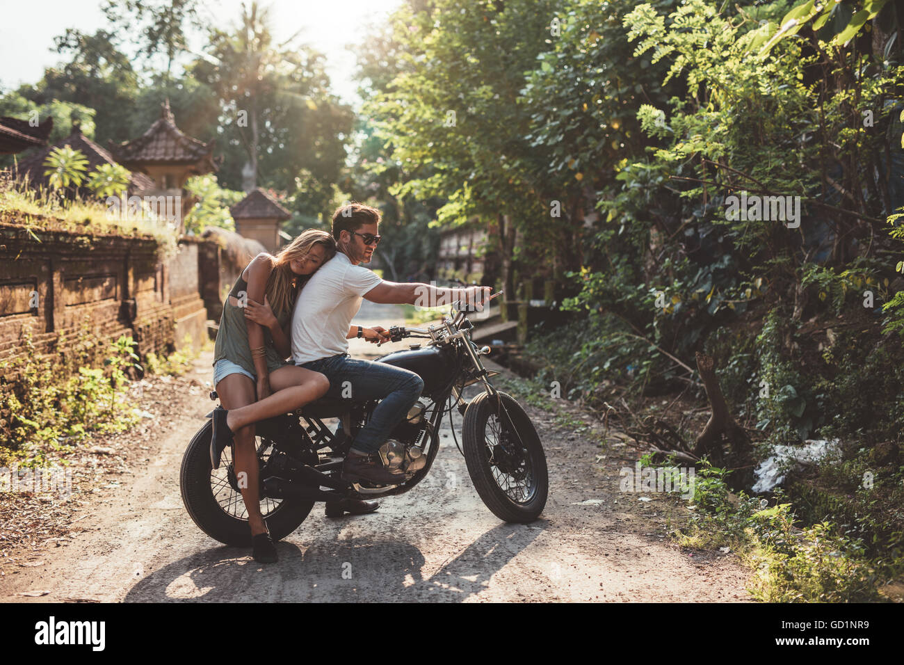 Loving young couple on a motorcycle. Young man and woman on motorbike in a village on a summer day. - Stock Image
