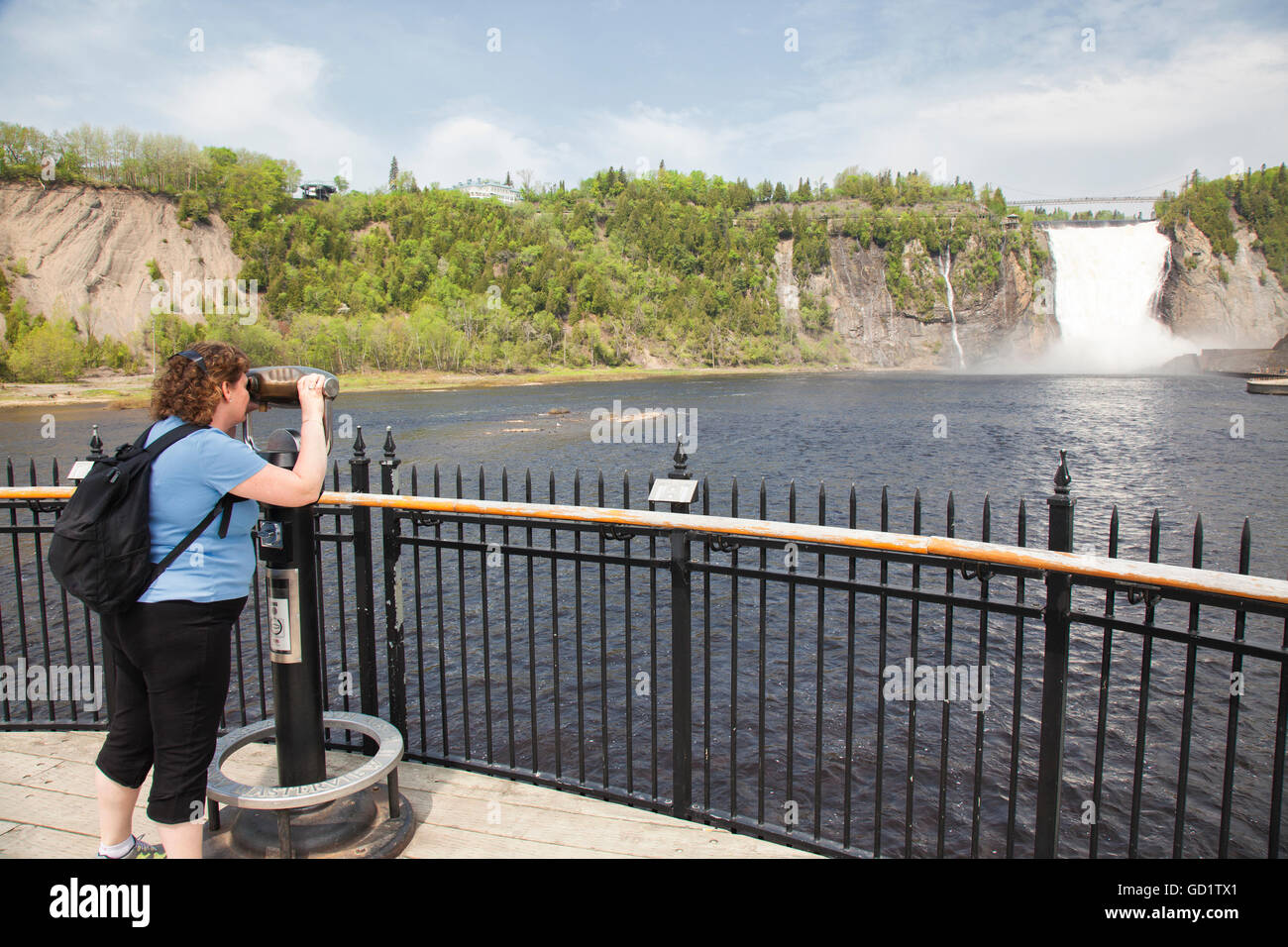 woman female tourist looking view scope at attraction montmorency falls waterfall in quebec - Stock Image