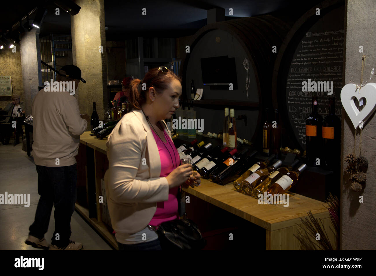 Visitors peruse selections of Alsatian wines at Zeyssolff Winery in Gertwiller, France. - Stock Image