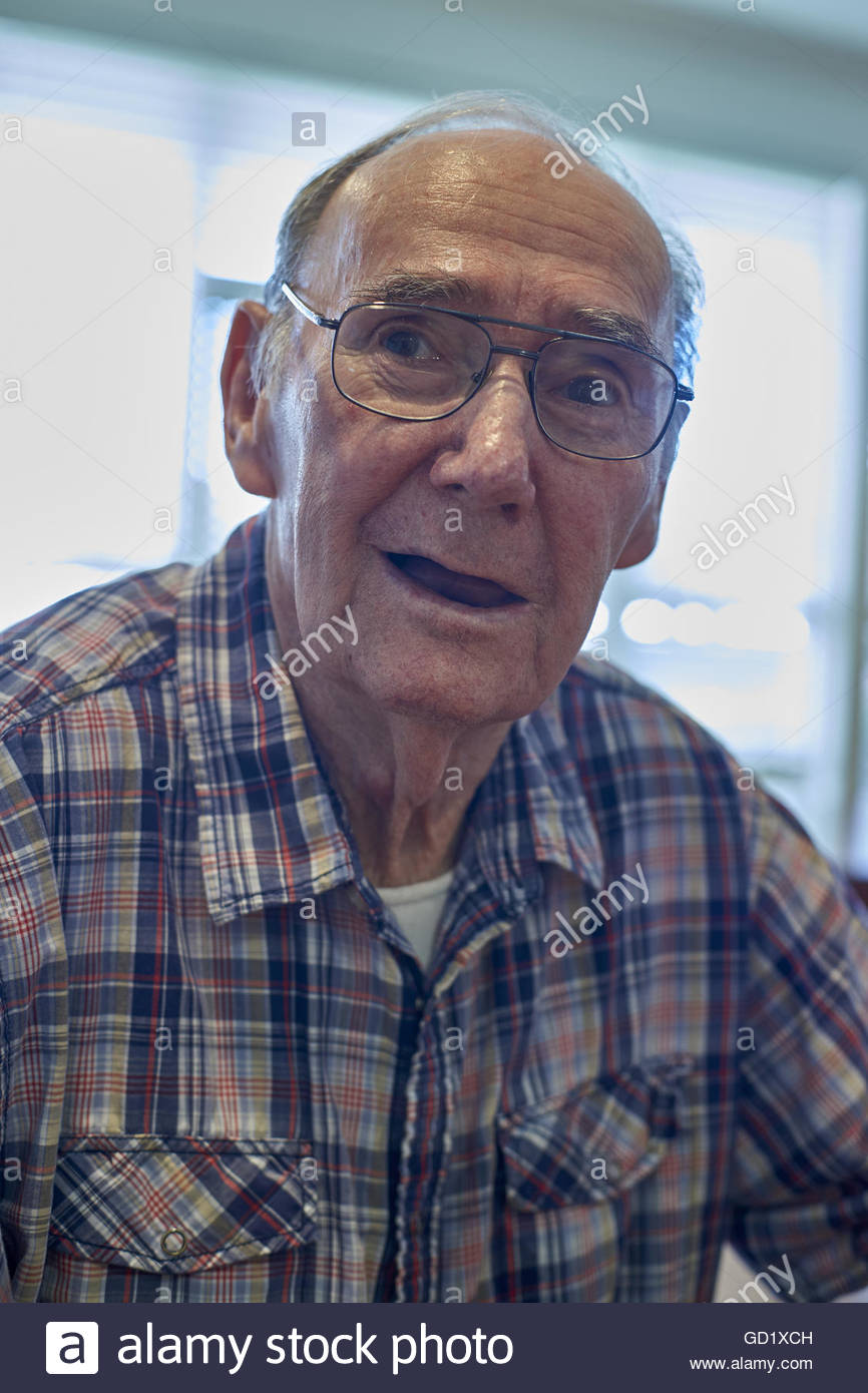 The open-mouthed, vacant stare of a dementia patient. An old man wearing glasses and a dress shirt -suffering Alzheimer's - Stock Image