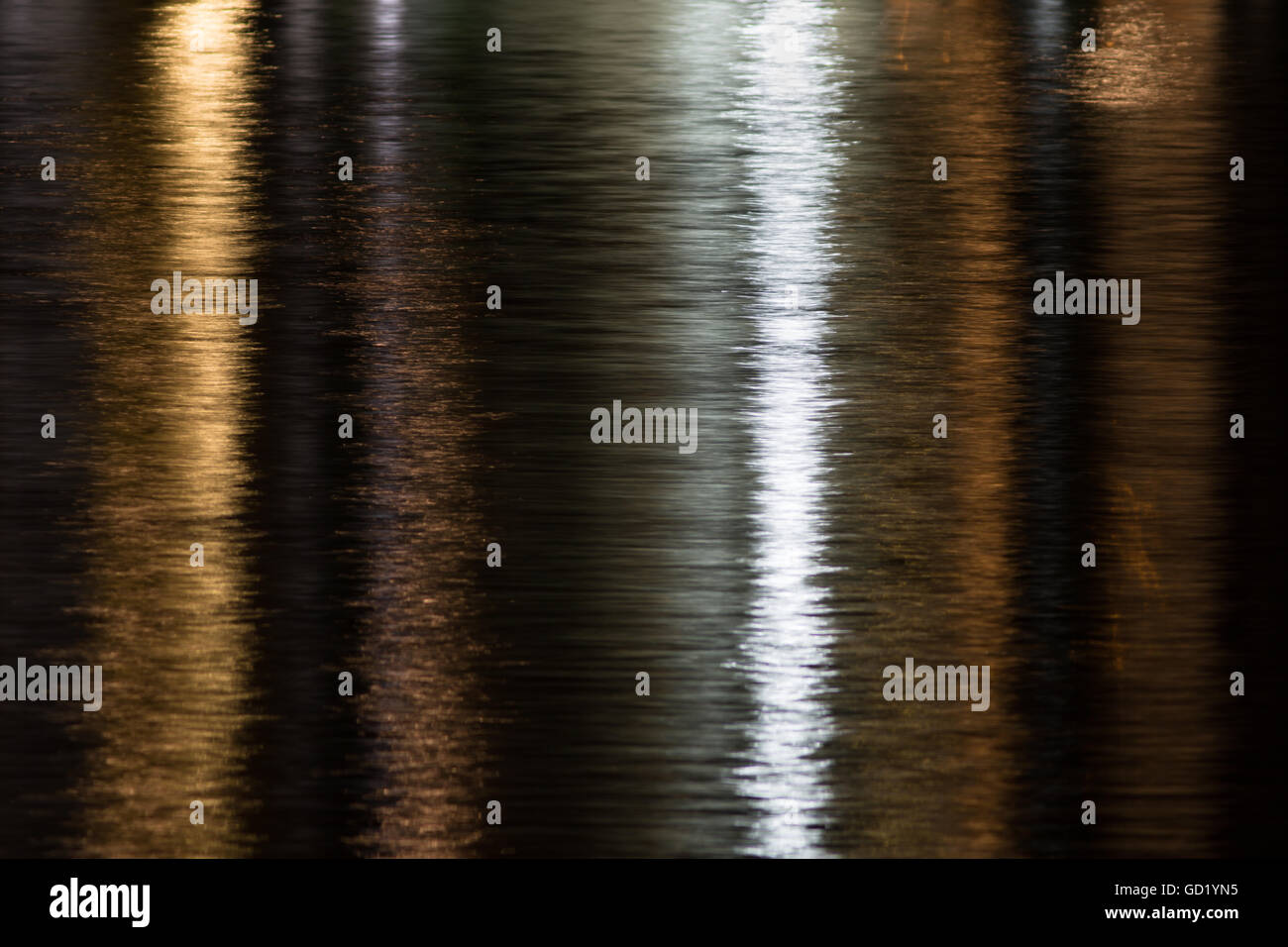 Reflection of yellow and white city lights shimmering on water in yellow and silver at night. - Stock Image