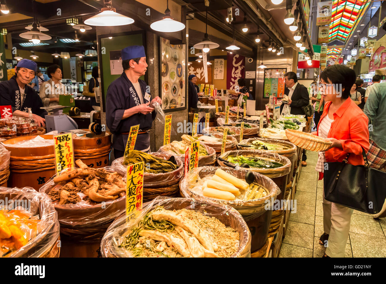 Shopper with basket considers purchase at local Japanese food stall, Nishiki Market, Downtown Kyoto, Japan, Asia - Stock Image