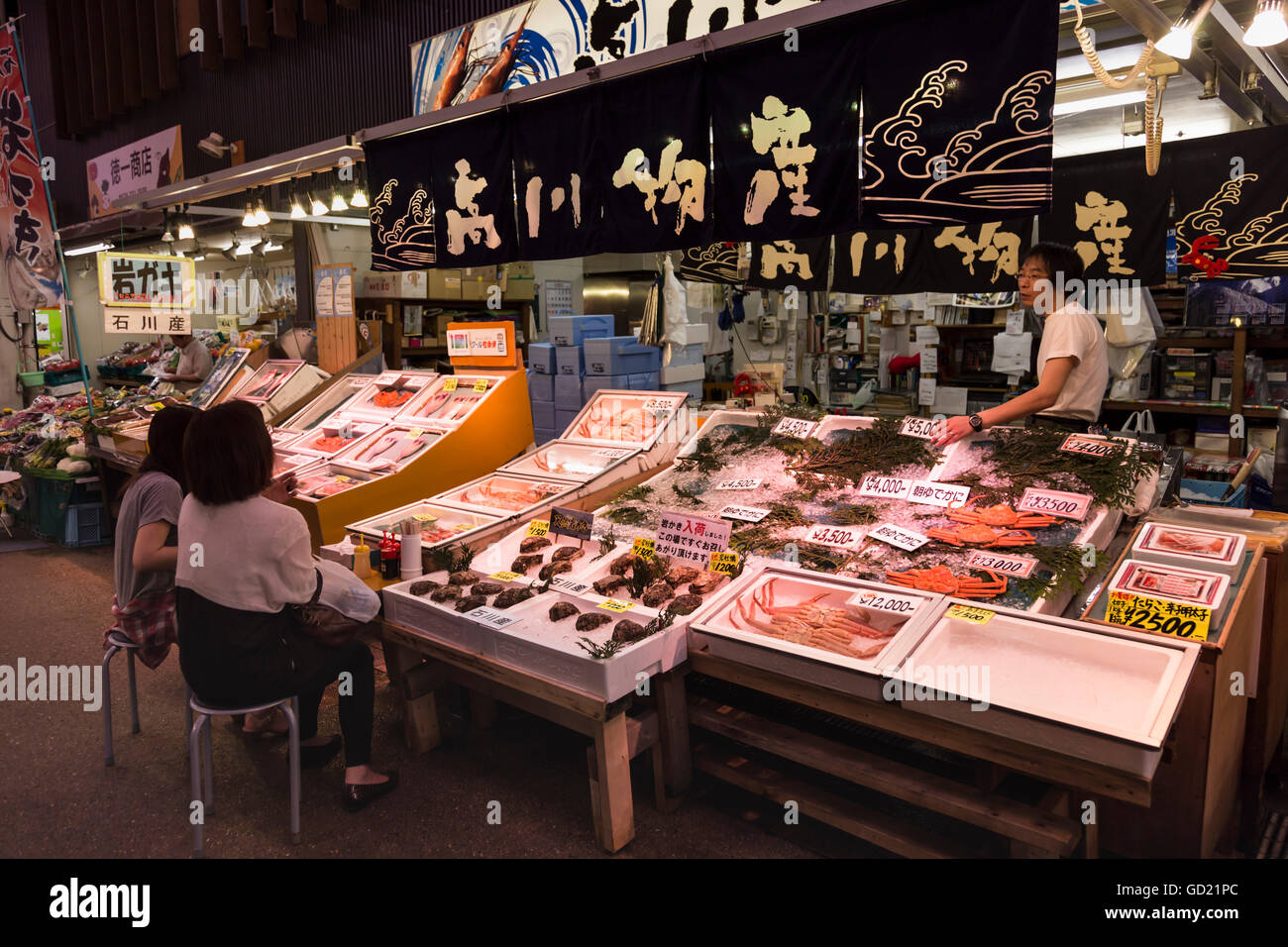 Diners sit and talk to seafood stall owner, Omicho fresh food market, network of covered stall lined streets, Kanazawa, - Stock Image