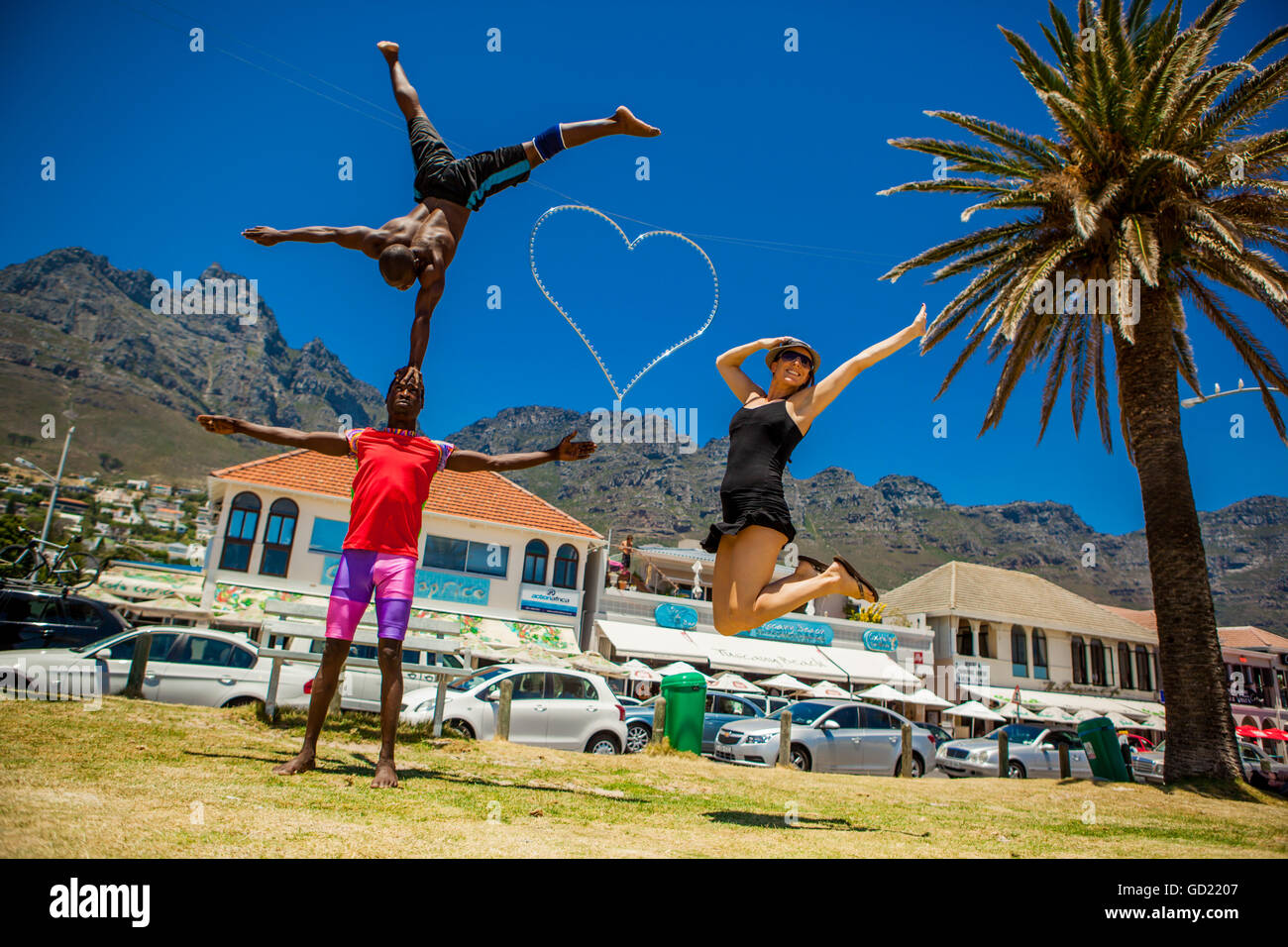 Laura Grier jumping with African acrobats, Camps Bay, South Africa, Africa - Stock Image
