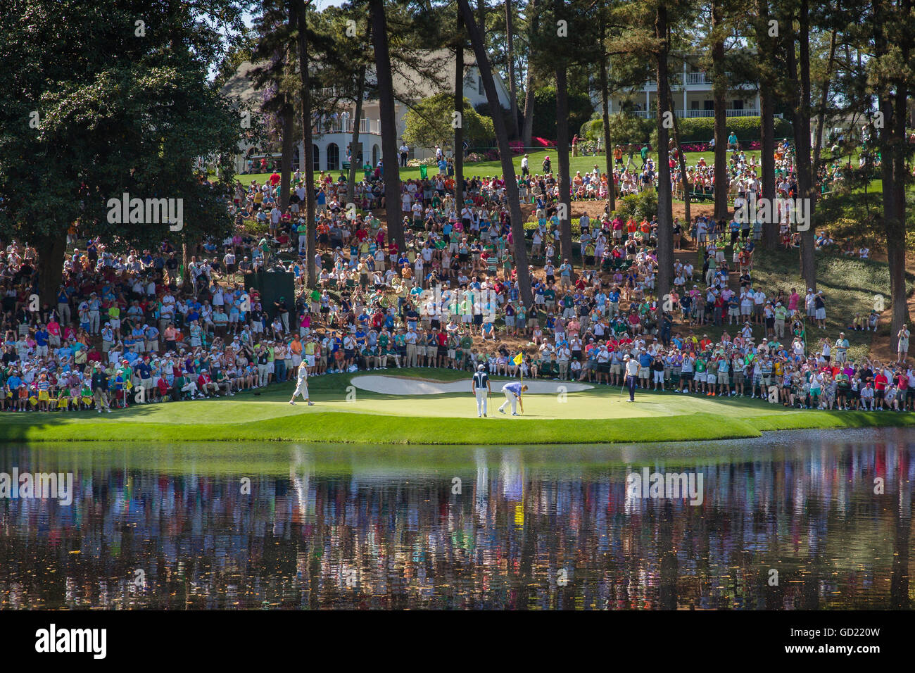 Spectators fill the hill behind the 9th green as players finish their round at Augusta National Golf Club, Augusta, - Stock Image