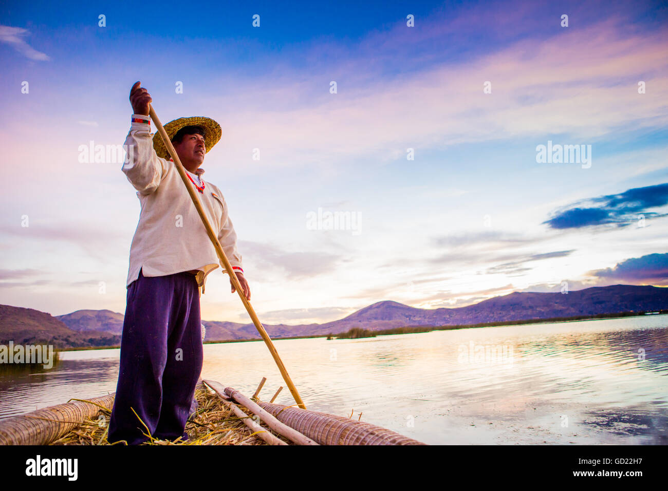 Quechua man rowing a boat on the Floating Grass islands of Uros, Lake Titicaca, Peru, South America - Stock Image