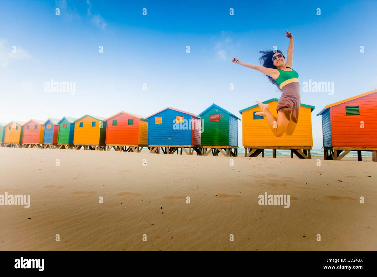 Laura Grier jumping in front of colorful beach huts, Muizenberg Beach, Cape Town, South Africa, Africa - Stock Image