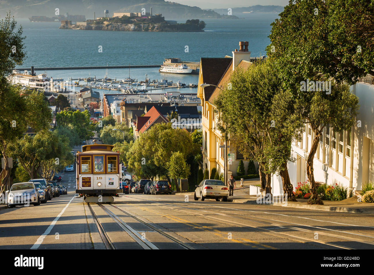 San Francisco city tram climbs up Hyde Street with Alcatraz beyond, San Francisco, California, United States of - Stock Image