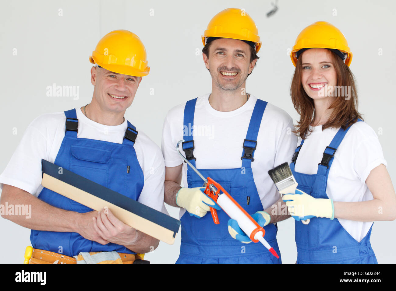 Three smiling workers wearing hardhats with different tools - Stock Image