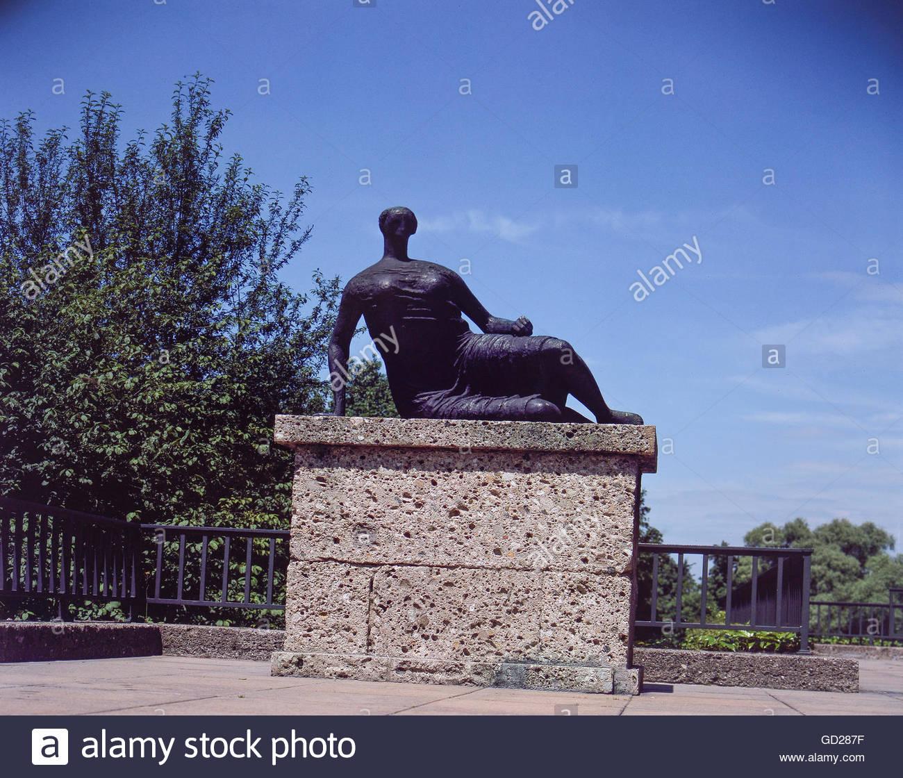 fine arts, Moore, Henry (1898 - 1986), sculpture, 'Grosse Liegende', bronze, 1957, in front of the Neue - Stock Image
