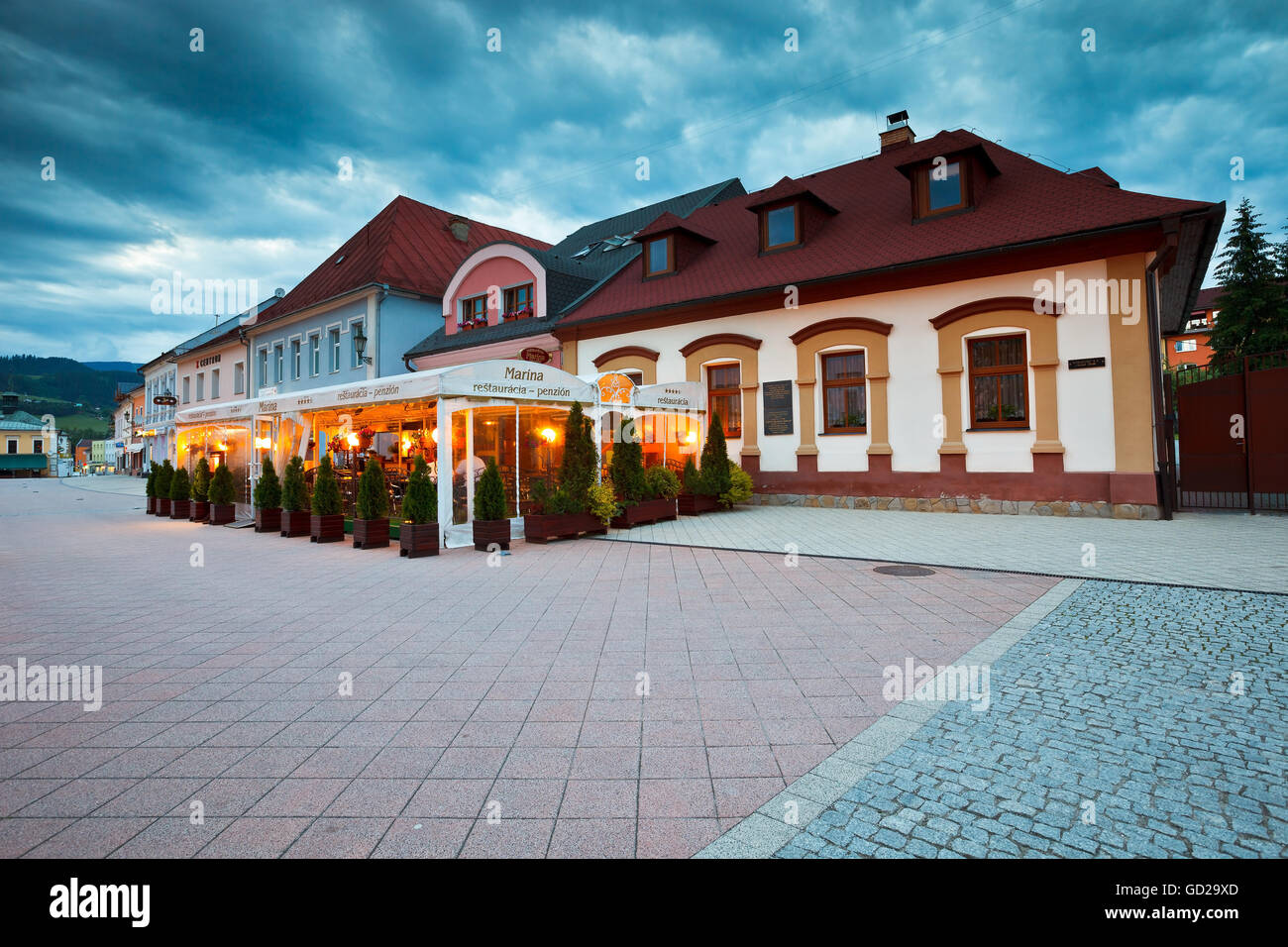 Pubs in the main square of Dolny Kubin late in the evening. - Stock Image