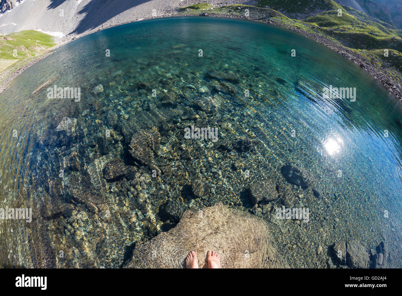 Fisheye view from above of alpine transparent lake and human feet into the water, in idyllic uncontaminated environment - Stock Image