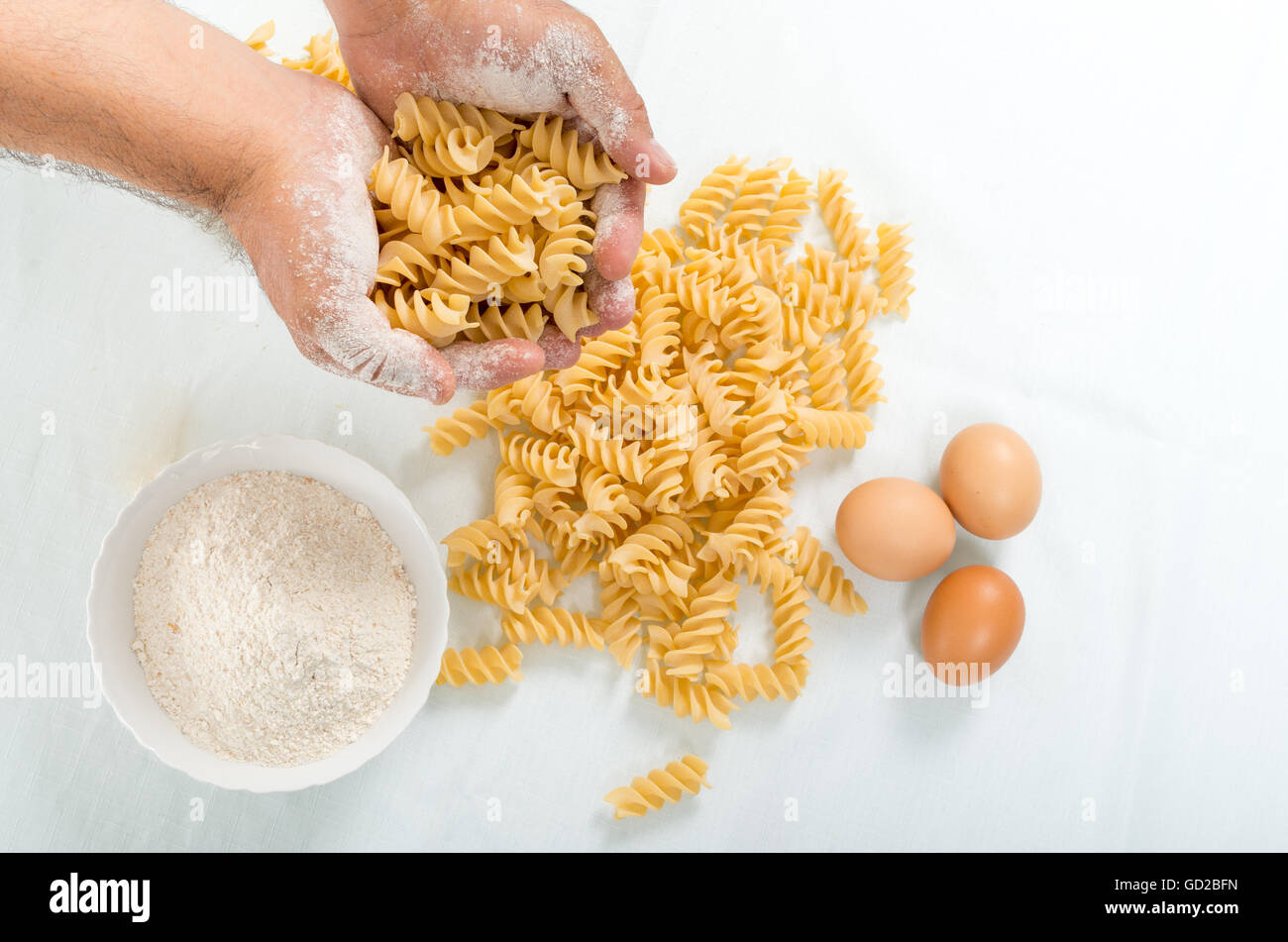 Male hands holding handmade rustic pasta - Stock Image