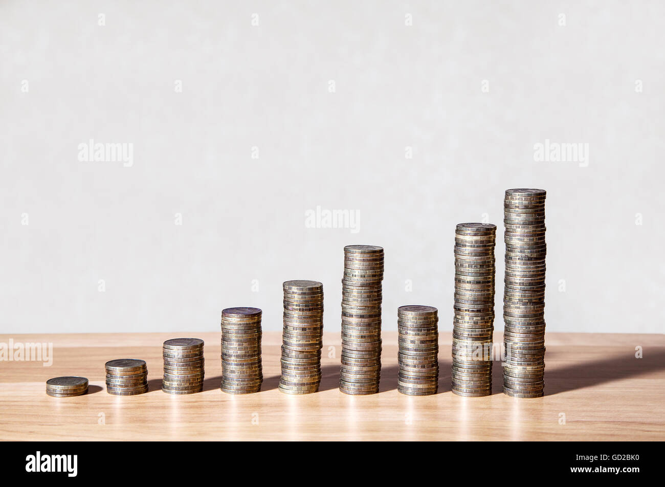 columns of coins on the table as a chart of growth closeup - Stock Image