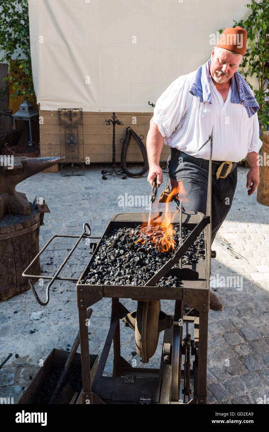 Friedberg, Germany - July 09, 2016: A man dressed in traditional costume is working as a blacksmith in the traditional - Stock Image