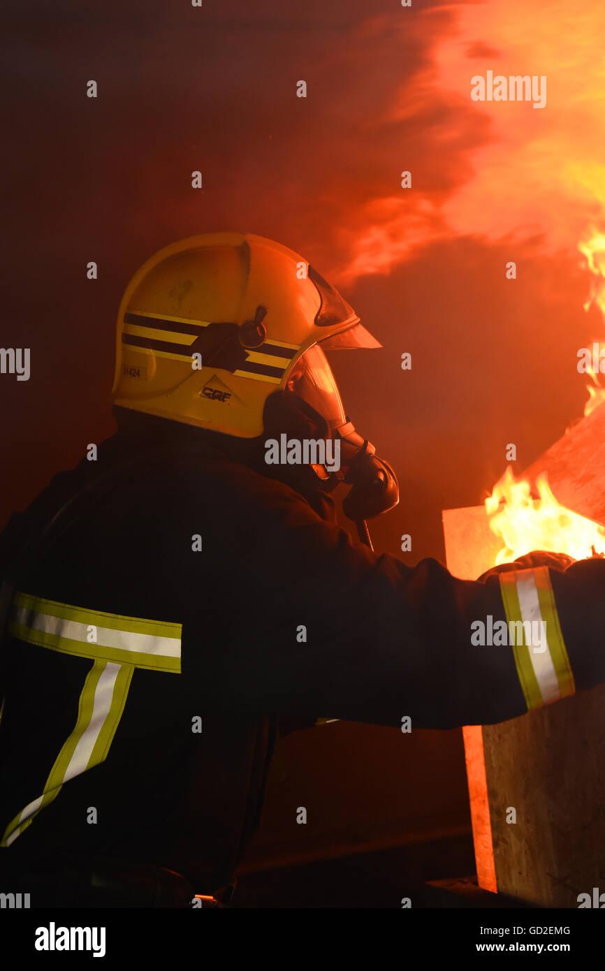 fire service. UK. Great Britain. fireman tackles a blaze - Stock Image