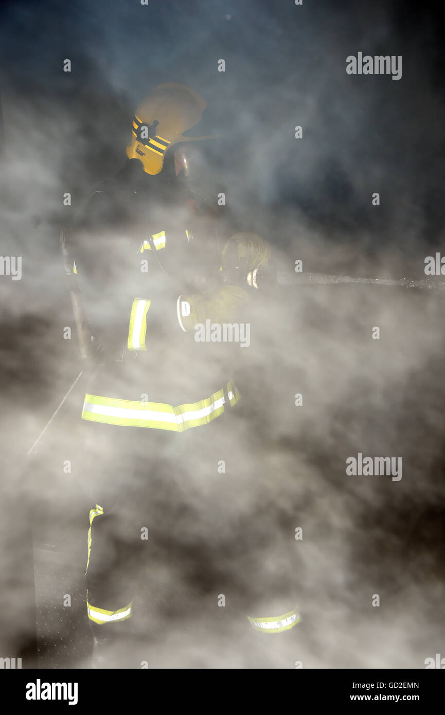 fire service. UK. Great Britain. Firefighter in smoke filled room - Stock Image