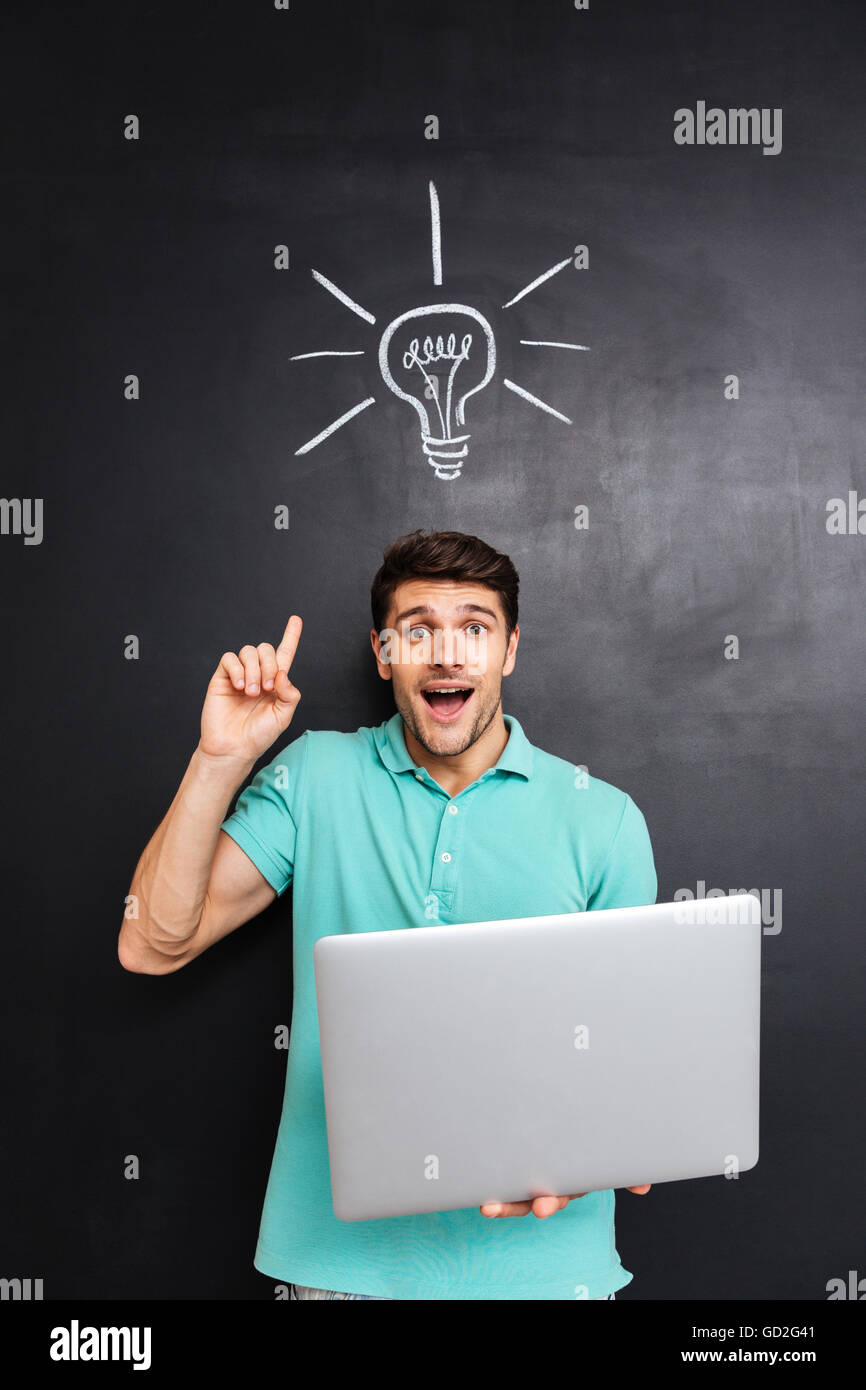 Excited young man pointing finger up and holding laptop over blackboard background with drawn light bulb - Stock Image