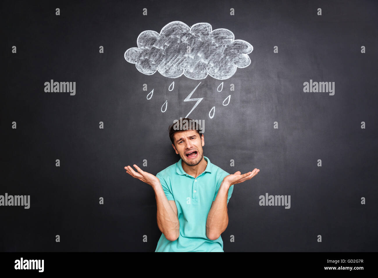 Sad young man crying over black blackboard with drawn raincloud - Stock Image