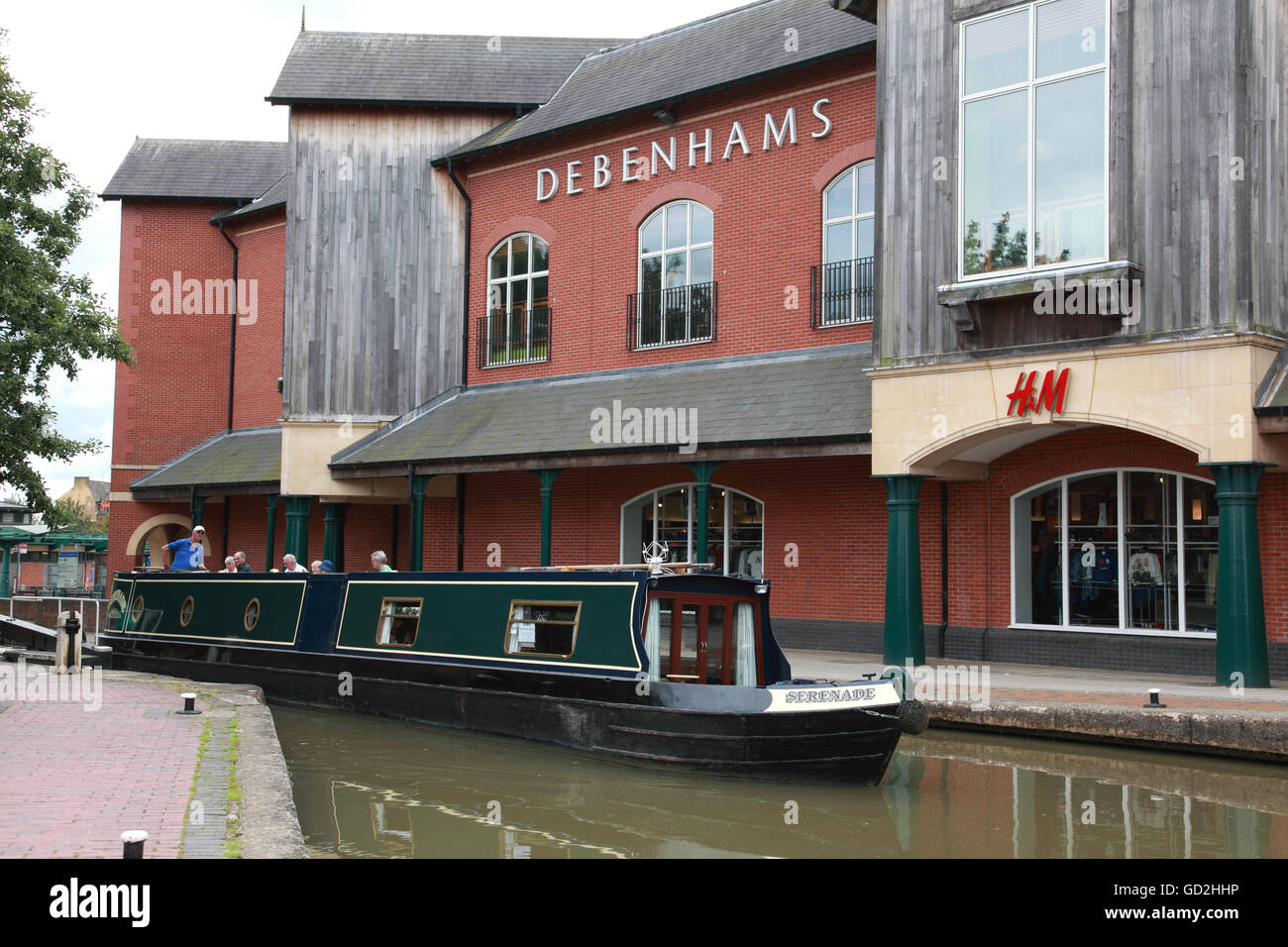 A narrowboat emerging from Banbury Lock on the Oxford Canal in front of the Castle Quay shopping centre. - Stock Image