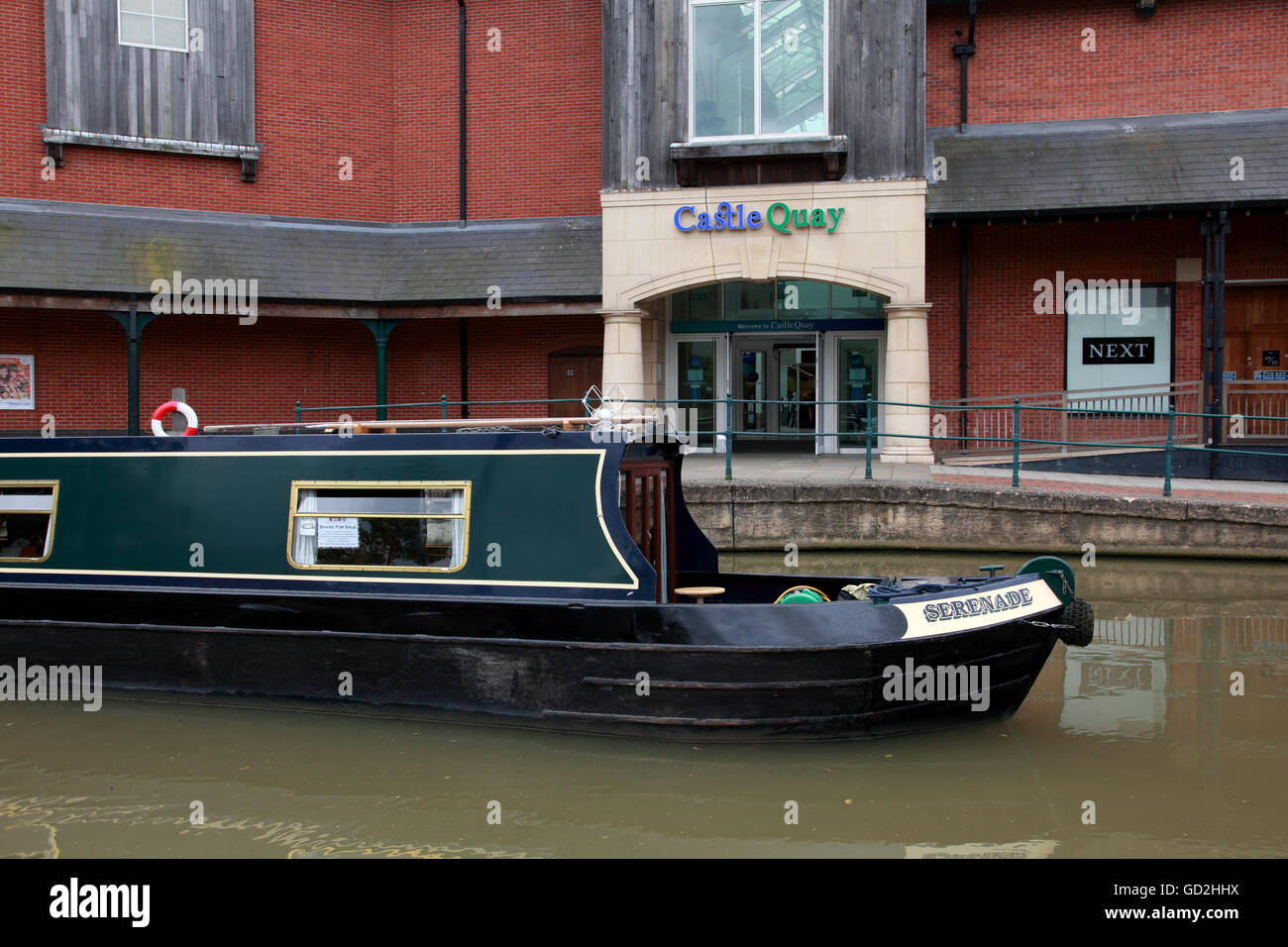 A narrowboat next to Banbury Lock on the Oxford Canal in front of the Castle Quay shopping centre. - Stock Image